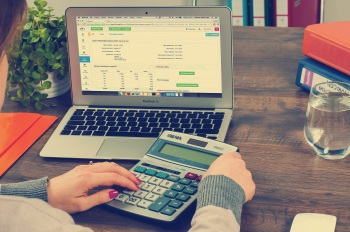Woman Calculating Benefit of Custom Portfolio on Personal Finances