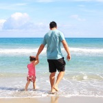 Daughter and Man Living Off Income from Investment Portfolio at Beach