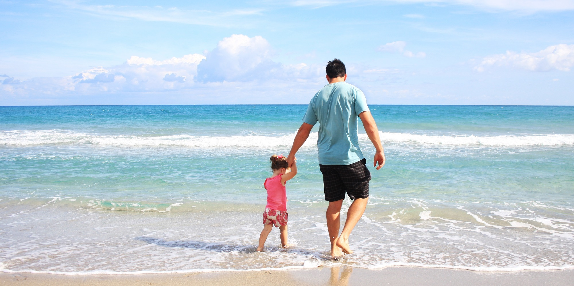 Man Living Off Dividends from High Equity Yield Portfolio Walking with Daughter on Beach
