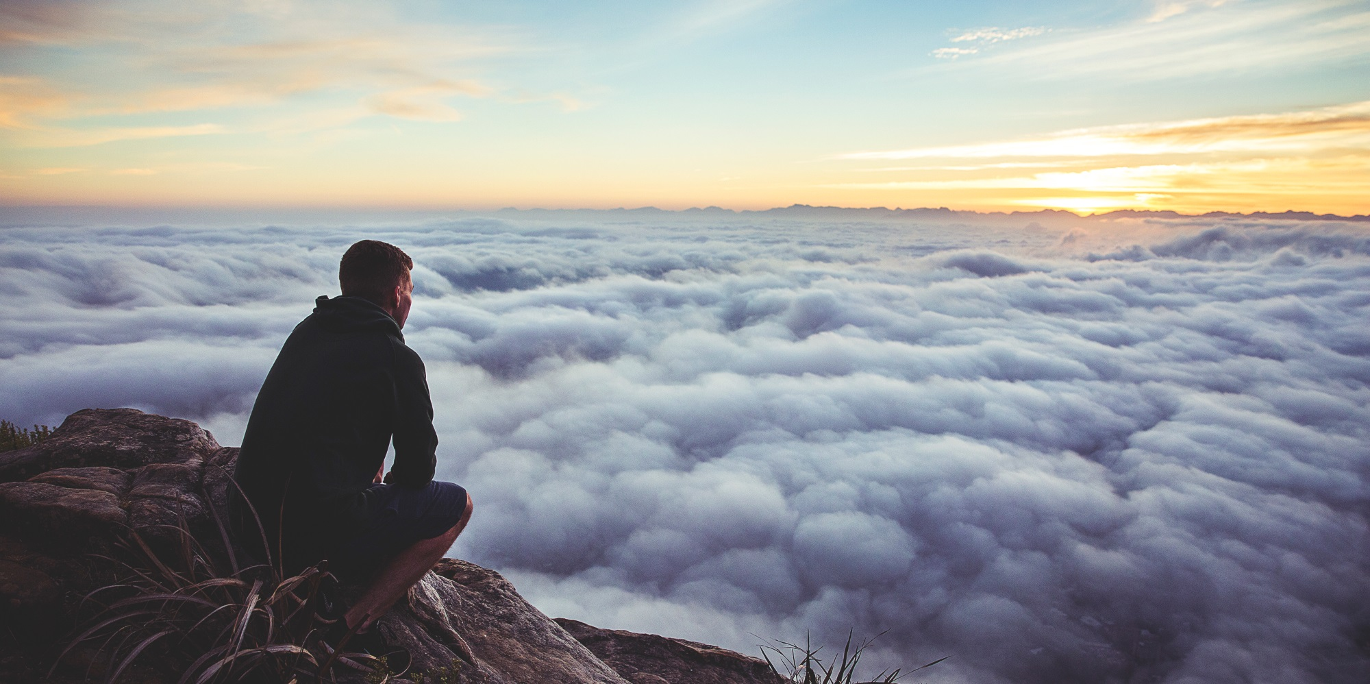 Man on Mountaintop Representing Legacy Portfolio Receiving New Vision from Financial Advisors